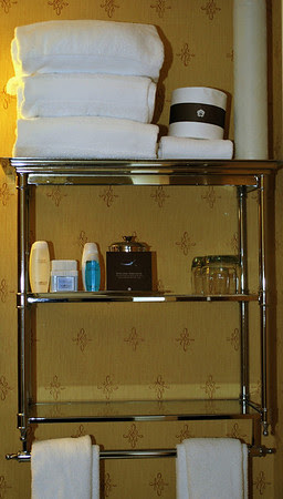 Bathroom shelves stocked with amenities and extra fluffy towels.