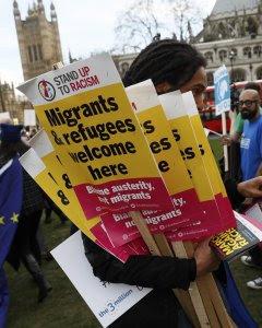 Un manifestante sujeta varias pancartas durante la manifestación en defensa de los inmigrantes en Londres. - REUTERS