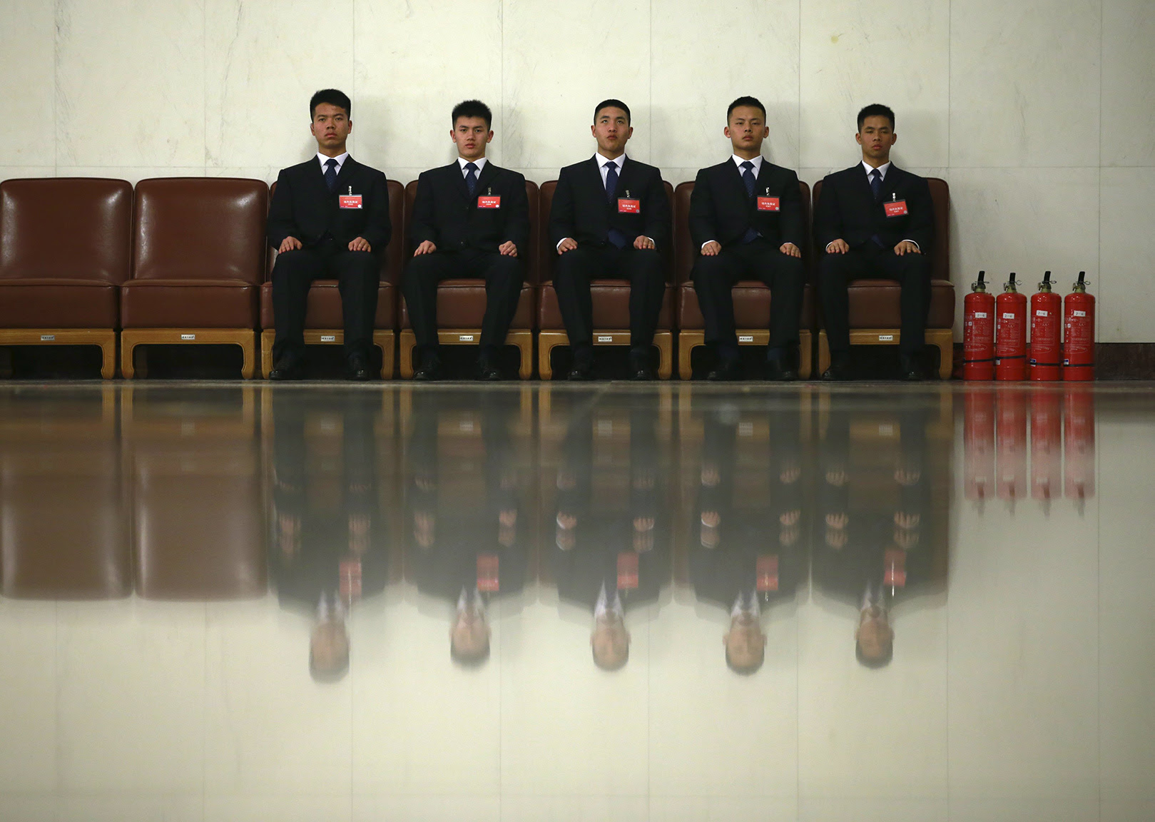 Security officers sit inside the Great Hall of the People before the opening session of the Chinese People's Political Consultative Conference (CPPCC), in Beijing, China
