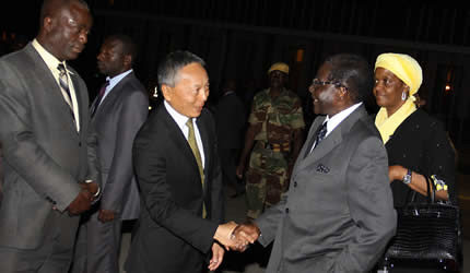 """Zimbabwe President Mugabe greets Japanese ambassador to the Southern African state as he boards a flight to Tokyo to participate in an international conference on Africa-Japanese relations. Zimbabwe maintains an official policy of """"look east."""" by Pan-African News Wire File Photos"""