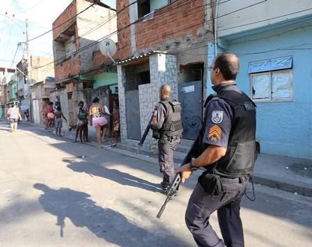Policiais patrulham a favela, enquanto moradores ficam na calçada por causa do forte calor
