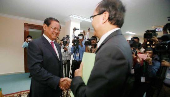 Interior Minister Sar Kheng shakes hands with opposition leader Sam Rainsy