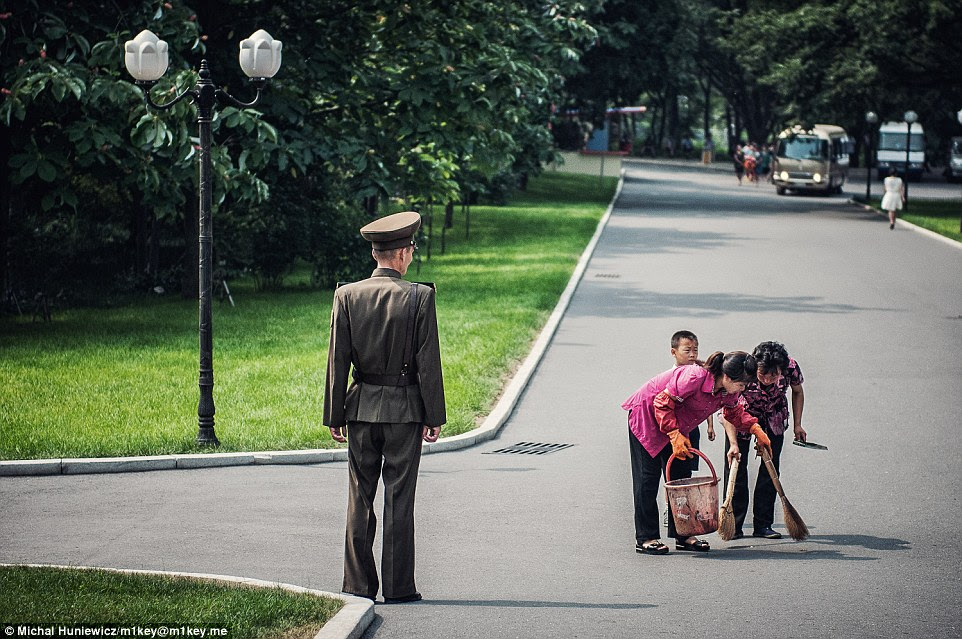 Watchful eye: Street cleaners sweep pavements for dust under the keen eye of a soldier in one of the parks in the capital city, Pyongyang