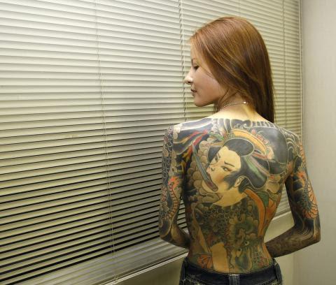 BERETNINGER: Shoko Tendo har skrevet bok om sin oppvekst i yakuzaen. Her viser hun fra tatoveringen som pryder ryggtavlen til mange av gjengmedlemmene. Foto: REUTERS/Kim Kyung-Hoon/NTB Scanpix