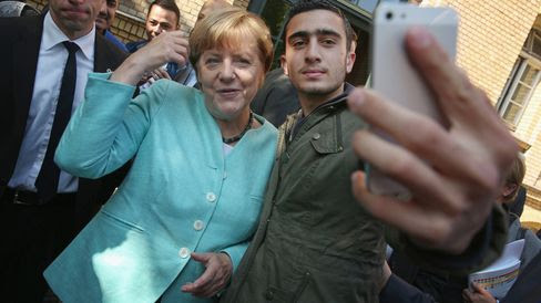German Chancellor Angela Merkel poses for a selfie with a migrant from Syria.