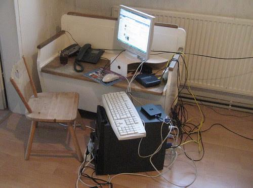 Photo: Bank und Sessel mit Telephon, Computer, Bildschirm, Anrufbeantworter und vielen Kabeln