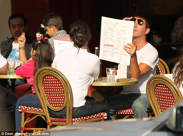 Simon Cowell raises his sunglasses so her can get a better look at the menu at Cafe Rouge