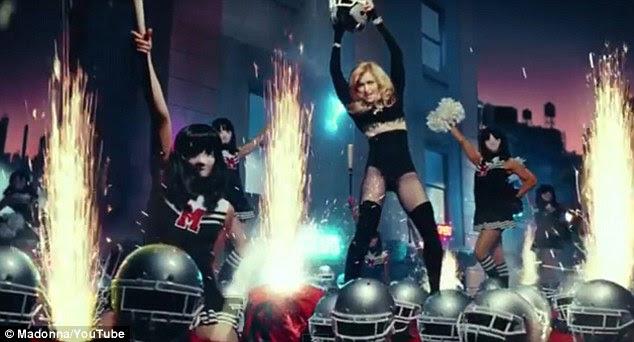 Explosão: Madonna segura o capacete no alto como os futebolistas começaram a explodir fogos de artifício todos ao seu redor