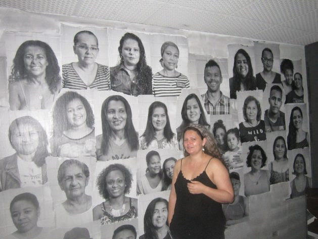 Cheila Patricia Souza, who participated in the São João 588 Occupation of an old hotel converted into housing for 80 families, stands in front of a collage of photos of the protagonists of the struggle for a home of their own, in the centre of São Paulo, Brazil. As in similar battles, most of the people involved were women. Credit: Mario Osava / IPS