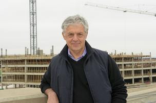 Fehmi Karahan's 300,000 square-feet of mixed use retail at Legacy West rises behind him.