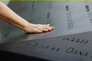 A woman places her hand on a name etched in the wall of one of the pools at the 9/11 memorial plaza in the World Trade Center site in New York Monday, Sept. 12, 2011, on the first day that the memorial was opened to the public. (AP Photo/Mike Segar, Pool)
