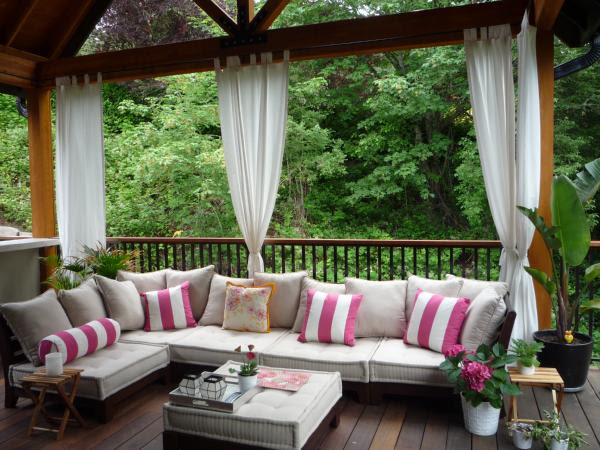 Outdoor living space white and pink striped pillows and outdoor furniture.