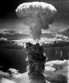 A gigantic mushroom cloud billowing over land in the 1940s