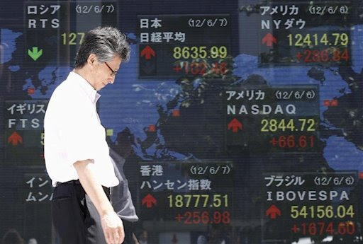 A man walks past a stock index board outside a brokerage in Tokyo