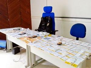Folhas de cheque com valores diferentes e R$ 1.254 em espécie (Foto: Polícia Civil)