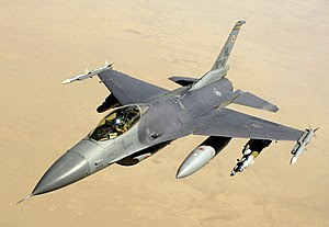 Aerial view of jet aircraft, carrying cylindrical fuel tanks and ordnance, overflying desert