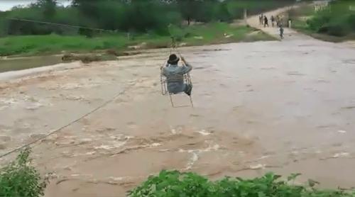 Cheia de rio faz população improvisar em travessia aérea