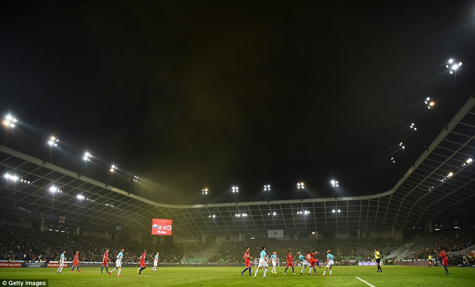A wide shot of the Stozice Stadium shows the scoreboard flashing 0-0; smoke from a yellow flare rises above the grass