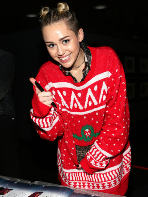 Taking a break from singing to sign some autographs at Jingle Ball in L.A., Miley rocked the coziest Christmas sweater ever!