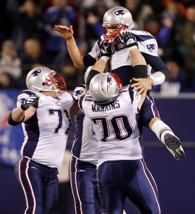 New England Patriots quarterback Tom Brady is lifted in the air by his teammates Logan Mankins (70) and Russ Hochstein, left, after Brady threw a 65-yard touchdown to Randy Moss in the third quarter of an NFL football game against the New York Giants at Giants Stadium in East Rutherford, N.J., on Saturday, Dec. 29, 2007. Brady broke the single-season record with his 50th touchdown pass and Moss broke the single season-record with his 23rd touchdown reception on the play.