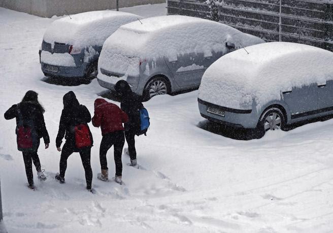 Un grupo de estudiantes caminan entre la nieve que se ha acumulado durante esta madrugada tras la intensa nevada que ha caído en la capital navarra