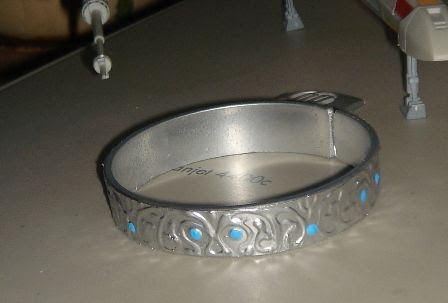 """From the lady who made this, """"First of all, it's not metal, it's plastic! As a result - a wonderful light weight and neat fitting. For the base I used an ordinary plastic cup for cold food. I cut the top of it with a metal-working saw (the plastic is rather thick, 3 mm), polished the cut with 2 different sandpapers, fused the edges. I put on the design with a 3D paint. Then, I painted the whole thing with an aerosol enamel. After drying I added the 'stones' with acryl paint."""""""