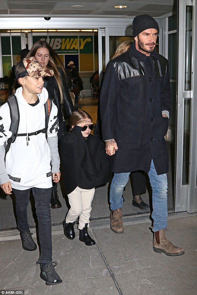 Jet-set look: The tot channelled her fashion designer mum's sense of style with a chic black cape teamed with chinos and leather ankle boots finished off with shades