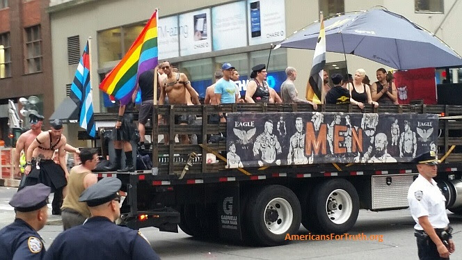"""Homosexual Sadomasochistic """"Pride"""" - Brought to You by Walmart: This float for the New York city homosexual """"leather"""" bar The Eagle rolls down Fifth Avenue at the New York City """"Pride"""" parade Sunday. Note the black-and-blue flag at left symbolizing """"leather pride""""--the S&M counterpart to the rainbow-colored flag symbolizing """"gay pride."""" Sadistic/masochistic """"leather"""" sex involves extreme behaviors that glorify domination, brutality and human degradation. This includes """"master-slave"""" couplings in which one partner becomes the """"sex slave"""" of another """"master."""" Homosexual leathermen revel in some of the vilest practices invented by mankind, including hand-arm-rectal """"fisting."""" Click to enlarge. Note the police looking on at lower left: one wonders what they are thinking. Photos may be reproduced provided credit given as follows: """"Photo: AmericansForTruth.org."""""""