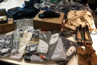 A group of items on a table including t-shirts in plastic bags, shoes, bags and a watch.