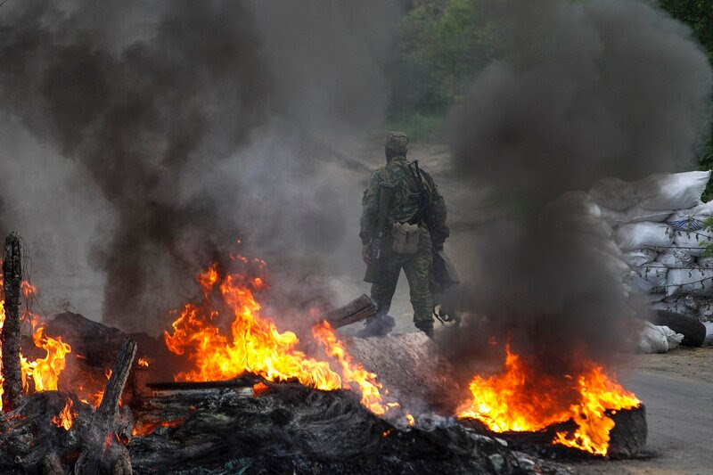 A pro-Russian separatist guards a checkpoint while walking near burning tyres near the town of Slaviansk