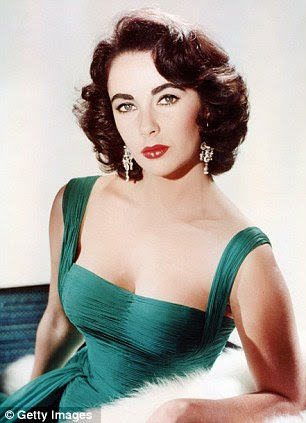Iconic: Elizabeth Taylor poses in a green low-cut dress, with a white fur wrap, circa 1950