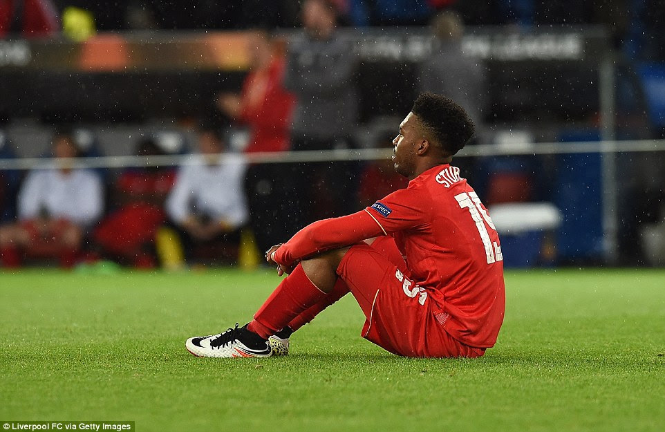 Sturridge struggles to hide his disappointment as he sits in the rain while Sevilla players celebrate victory around him