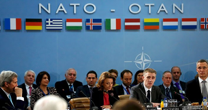 Montenegro's Foreign Minister Igor Luksic (at table, 2nd R) delivers remarks with Defense Minister Milica Pejanovic (3rd R) after Montenegro was welcomed as a new member at the NATO ministerial meetings at the NATO headquarters in Brussels December 2, 2015