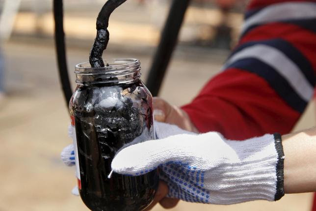 Oilfield workers collect a crude oil sample at an oil well operated by Venezuela's state oil company PDVSA, in the oil rich Orinoco belt, near Morichal at the state of Monagas April 16, 2015. REUTERS/Carlos Garcia Rawlins