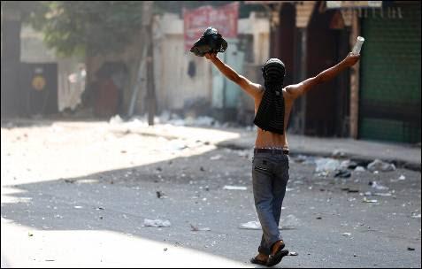 Un partidario del derrocado Mohamed Mursi, durante los enfrentamientos con los opositores al expresidente egipcio, fuera de la estación de Policía cerca de la Plaza Azbkya Ramses en El Cairo.