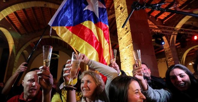Varias personas celebran los resultados de las elecciones del 21-D en la sede de la Asamblea Nacional Catalana (ANC) en Barcelona. REUTERS / Albert Gea