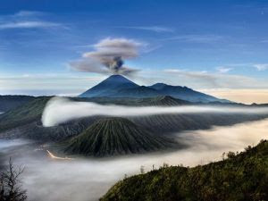 """NGC Beautiful Indonesia - Mount Semeru and Bromo """"Some Indonesians believe that belching volcanoes such as Mount Semeru (in background) and Mount Bromo (in foreground) are portals to a subterranean world that has shaped not only Indonesia's landscape but also its beliefs and culture. A long exposure time captured stars in this photo—and the brief balanced light from both a fading moon and a brightening eastern sky""""."""