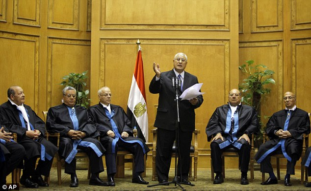 No time to waste: Adly Mansour (centre), the chief justice of Egypt's Supreme Constitutional Court, speaks at his swearing in ceremony as he is made interim president just hours after the coup