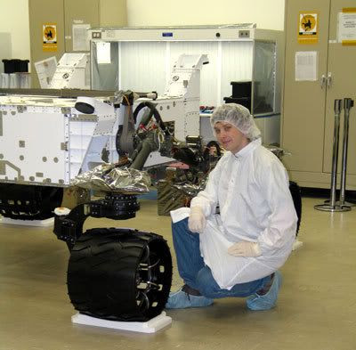 An engineer poses next to one of the wheels on the MARS SCIENCE LABORATORY.
