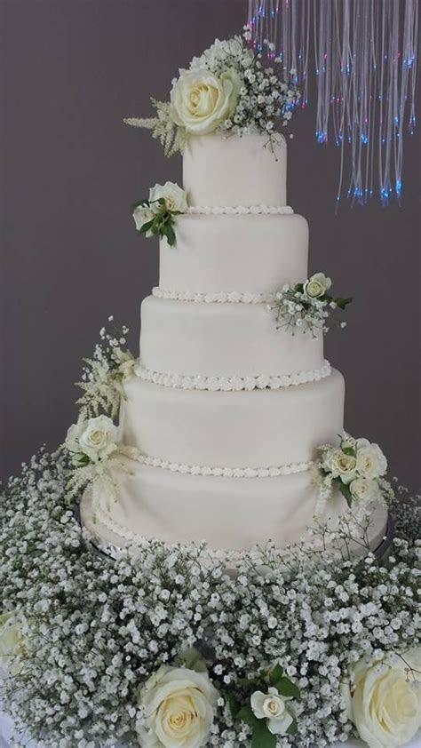 A 5 tier ivory iced wedding cake with fresh flowers (ivory