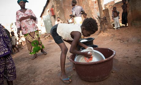 MDG : Slavery : A child (slave) washes dishes in a crowded a slum in Bamako, Mali
