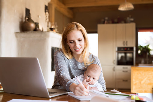 Mother with baby at home using laptop and taking notes : Stock Photo