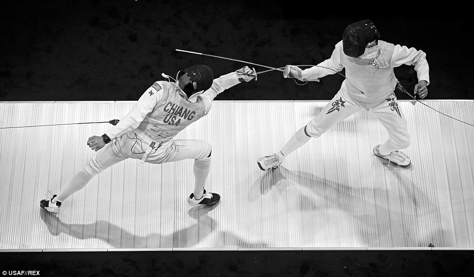 Fencing: Alex Chiang hits his opponent to score a point during a foil match at the 2014 NCAA Fencing Championships at Ohio State University in Columbus, Ohio. The foil is used as a thrusting weapon only. Contact with the side of the blade from a slap or slash does not result in a score. Foil is one of the three weapons of modern fencing, with the other two being ÈpÈe and sabre