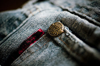 Closeup of a copper rivet on blue jeans.