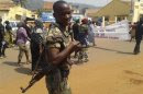 A soldier smiles as women march to protest against the conflict in their country in the streets of Bangui