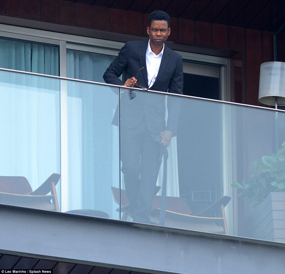 Star-studded: Actor and comedian Chris Rock appeared on the balcony of the luxury beachfront hotel, which the couple have paid $150,000 to hire for their famous friends