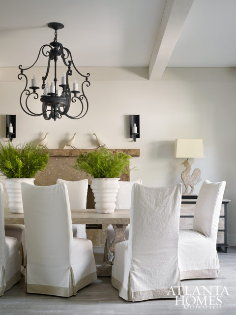 In the dining room, texture in the form of limewashed floors, a rough-hewn mantel and a light elm pedestal dining table and slipcovered chairs, both from Bungalow Classic, complicate the play on light. Carved rooster lamp from Parc Monceau.