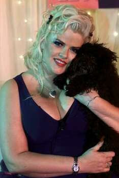 Smith poses, with her black toy poodle Sugar Pie, in 2002 during a media presentation of E! Networks The Anna Nicole Smith Show. Photo: DAMIAN DOVARGANES, Associated Press