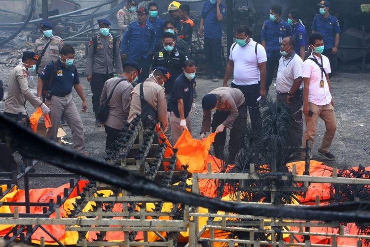 Personel Brimob Polda Metro Jaya mengevakuasi jenazah korban kebakaran pabrik kembang api di Kosambi, Tangerang, Banten, Kamis (26/10/2017). Kebakaran yang diduga akibat ledakan pada salah satu tempat pembuatan kembang api yang baru beroperasi dua bulan ini sedikitnya menewaskan 23 orang karyawan dan puluhan karyawan luka bakar.