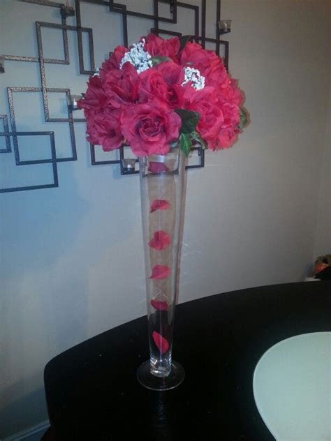 Red rose centerpiece with trumpet vase and falling rose